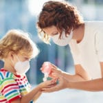 Mother and child wearing masks with hand sanitizer