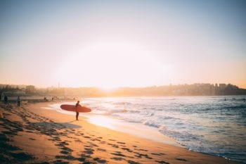 Healthcare in Australia: Man with a surfboard stands at the shore of Bondi Beach