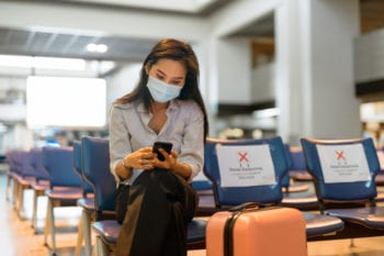 Woman with mask traveling during covid-19 pandemic