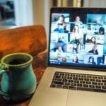Remote working fatigue: A green pottery mug sits next to an open laptop showing many people on a video calll