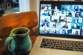 A green mug sits next to an open laptop showing people on a video call working remotely