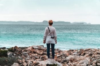 A Costa Rican expat stands on a rocky shoreline and looks over a light blue sea