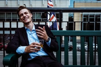 expats from UK: Young man in a suit relaxes on an outdoor patio with a beer and a British flag in the background