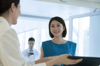 Chinese patient smiling at doctor in white coat