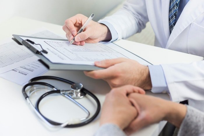 doctor taking notes stethoscope on table
