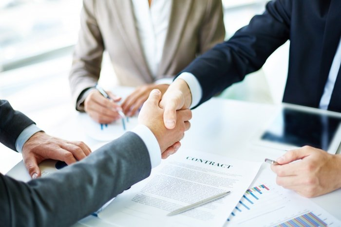 shaking hands over documents on table