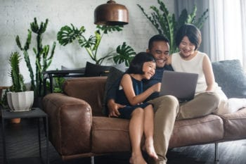 malaysian family sitting on sofa with laptop