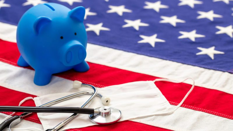 How do I save on health care costs in the USA? Piggy bank on American flag with medical gear