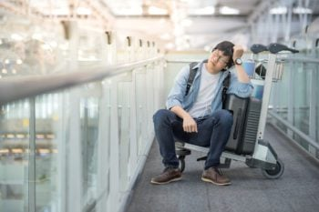 Aisan man sitting on luggage trolley, looking exhausted