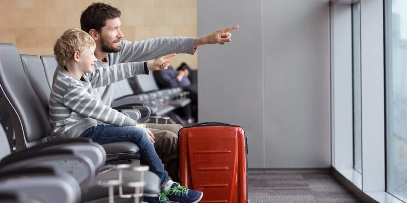 father and son waiting for their delayed international flight